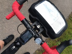 Road bicycle with red bar tape and handlebar bag with route map and notes