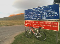 Giant road bike next to the Bealach na Ba road sign at Tornapress